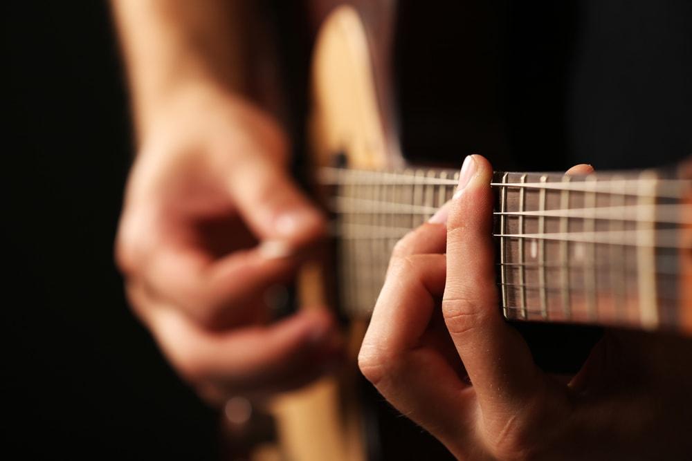 Due mani in primo piano che suonano la chitarra
