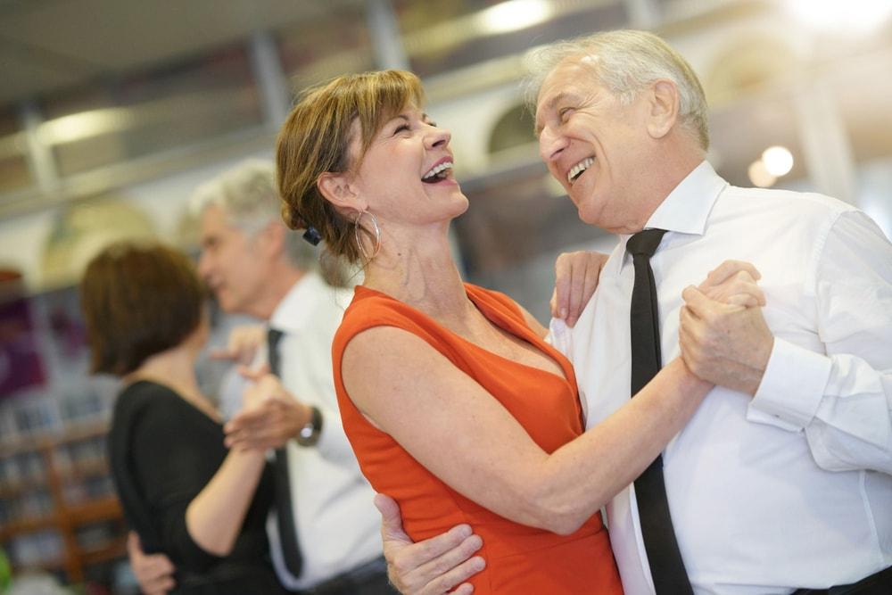Una coppia di uomo e donna che ballano sorridenti