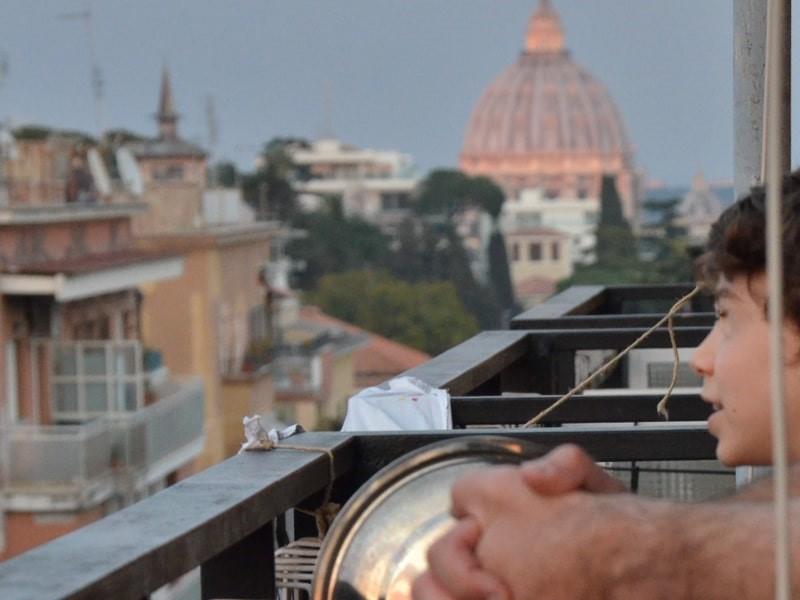 Un bambino sul terrazzo e la cupola di San Pietro