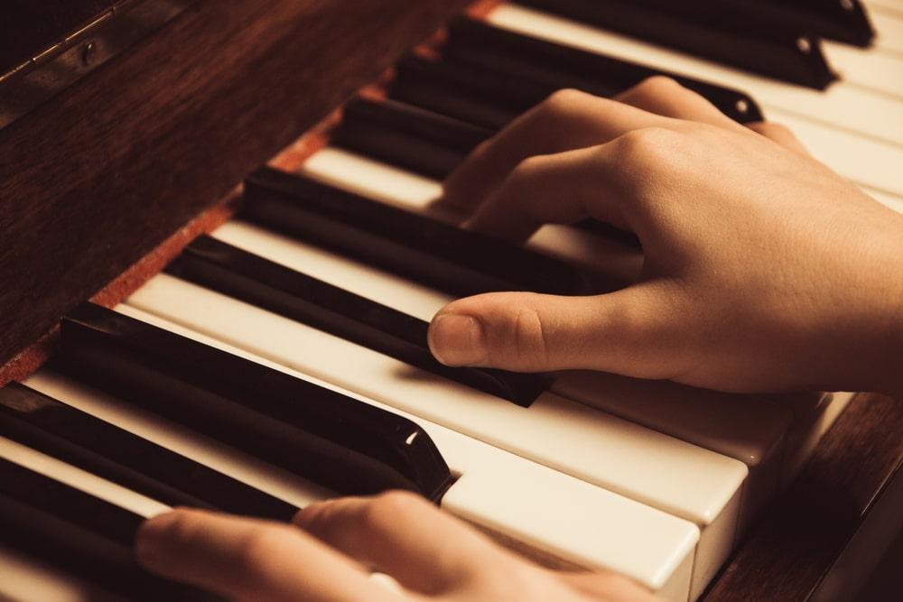 Mani che suonano su pianoforte