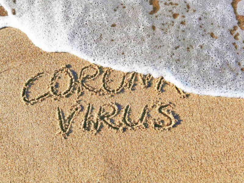 Le onde cancellano una scritta sulla sabbia