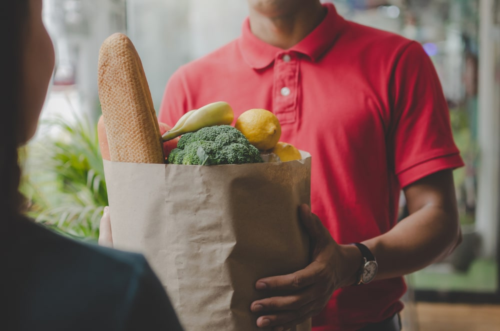 Mani che porgono un pacco di alimenti