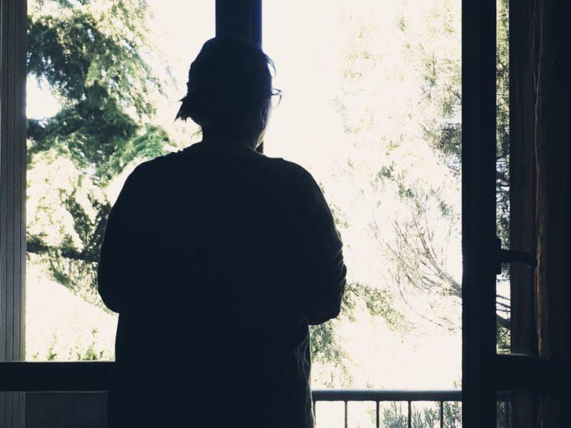 Una donna dentro casa che guarda dalla finestra