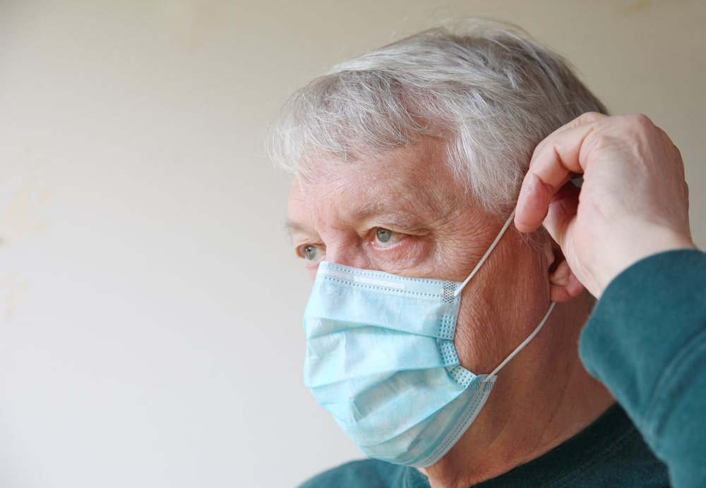 Senior che si mette mascherina anti-Covid
