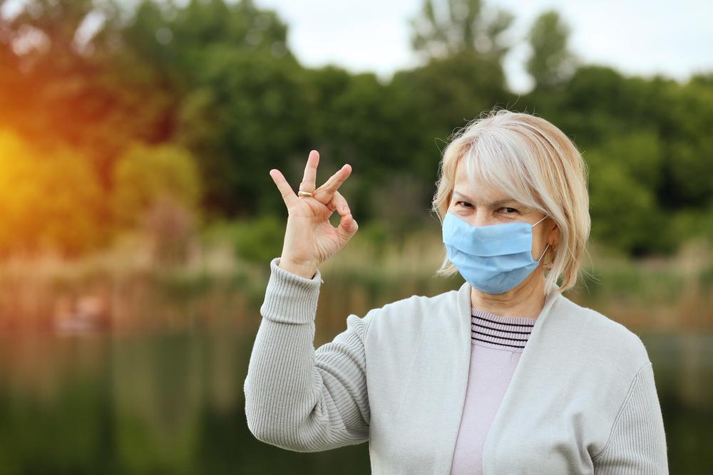 donna over 50 con mascherina. Gesto di speranza