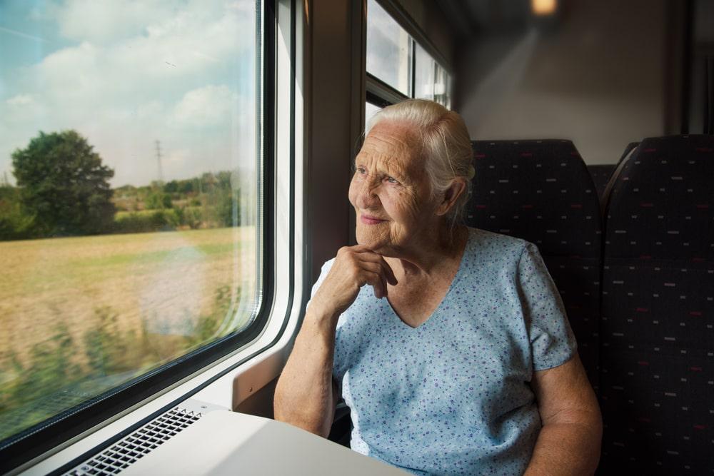 Senior in treno che guarda dal finestrino