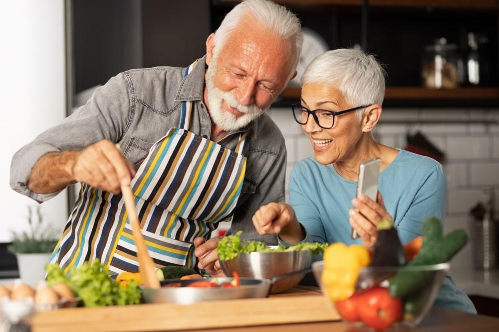 Coppia senior cucina piatti sani