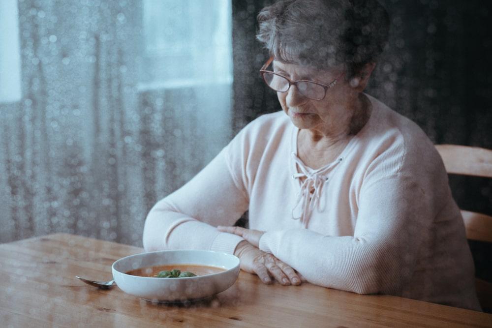 Persona anziana che mangia da sola