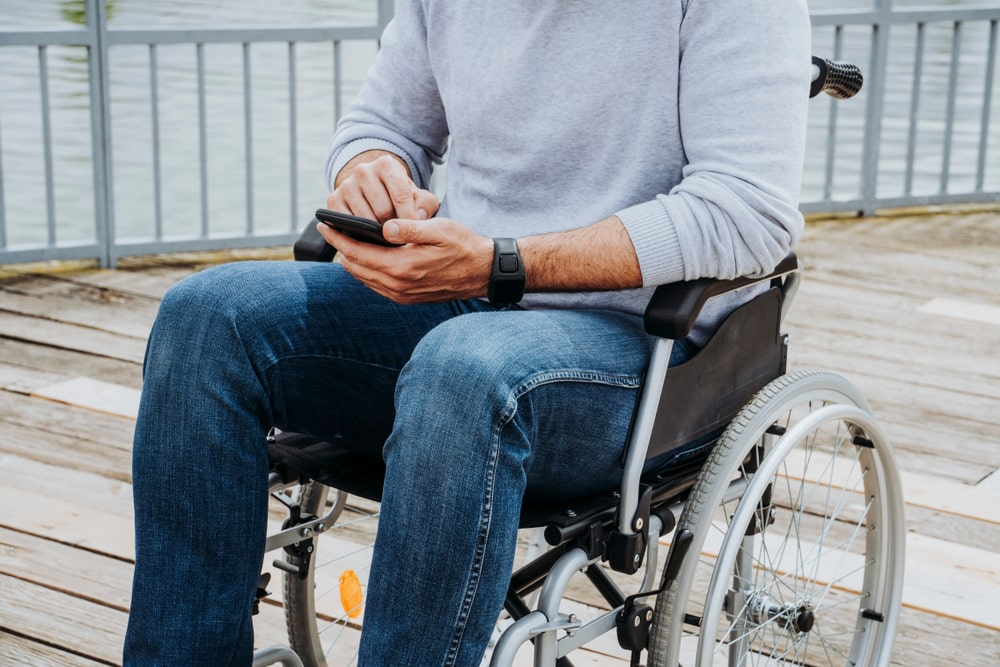 Uomo su sedia a rotelle con App