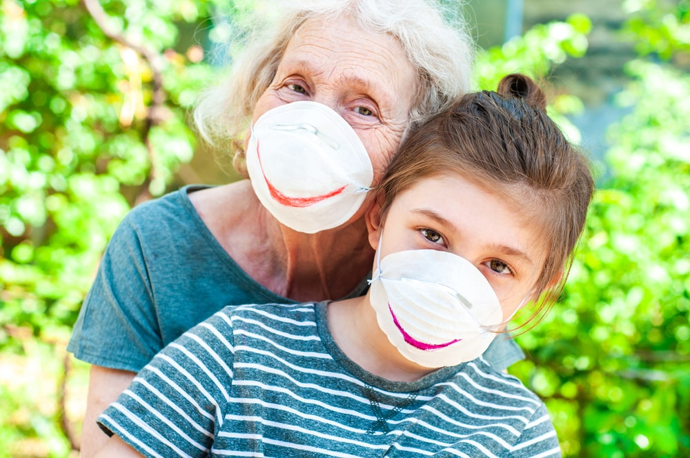 Nonna e nipote con mascherina con sorriso