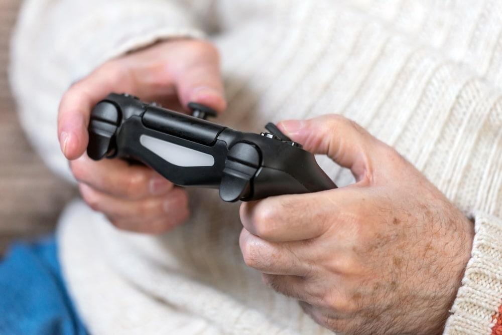 Senior tiene tra le mani controller di un videogame