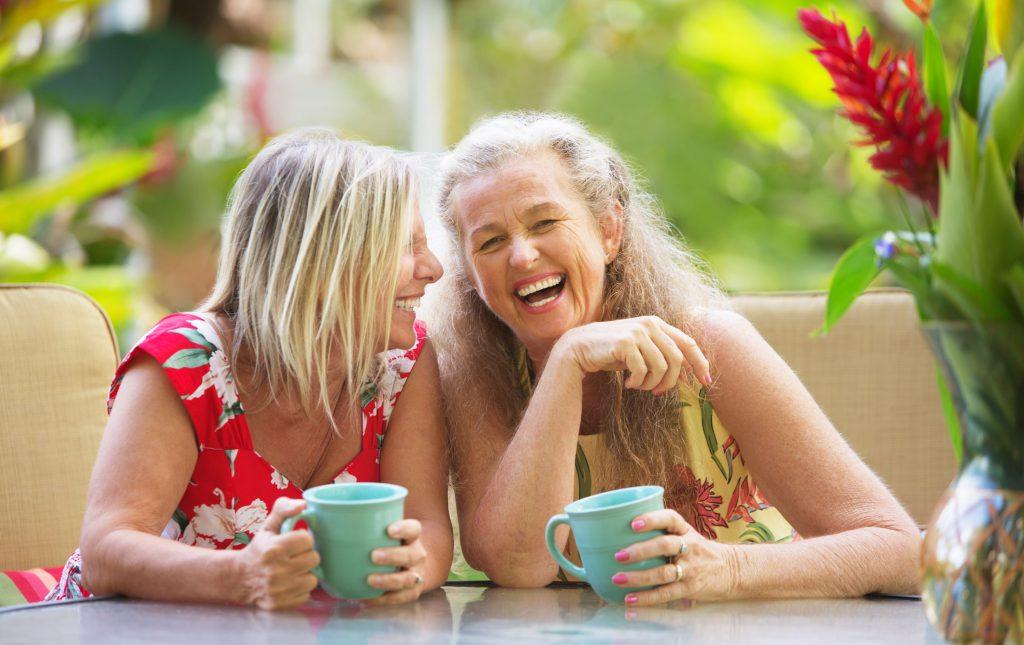 Due amiche ridono davanti ad una tazza di the