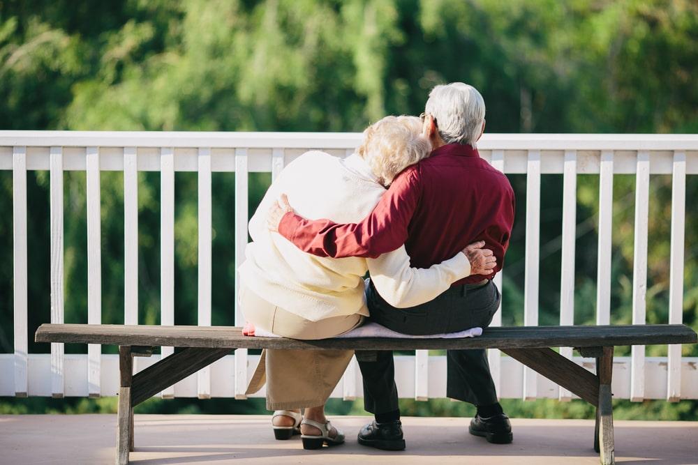 Coppia senior seduta e abbracciata