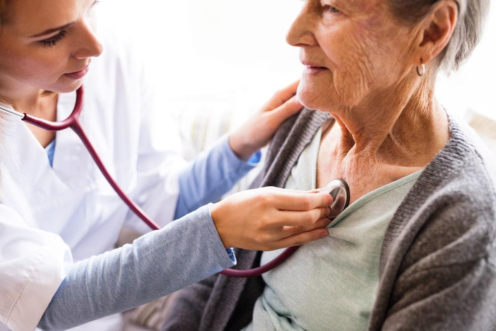 Dottoressa ausculta petto a donna senior