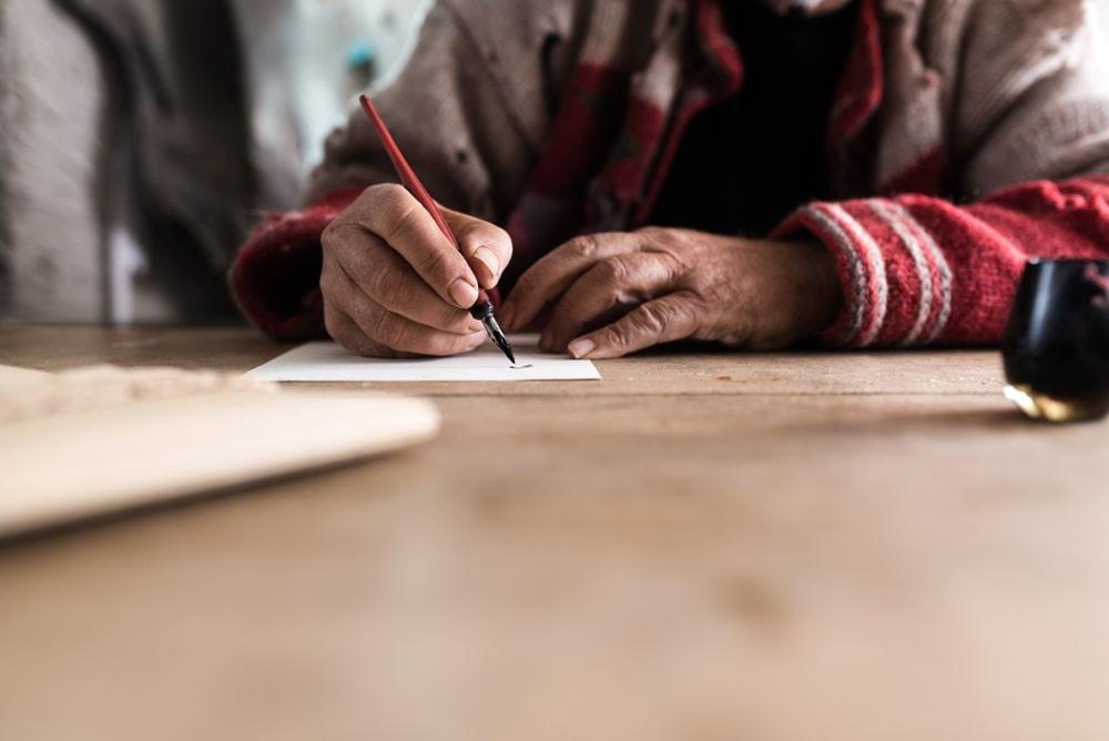 mani che scrivono una poesia con stilografica
