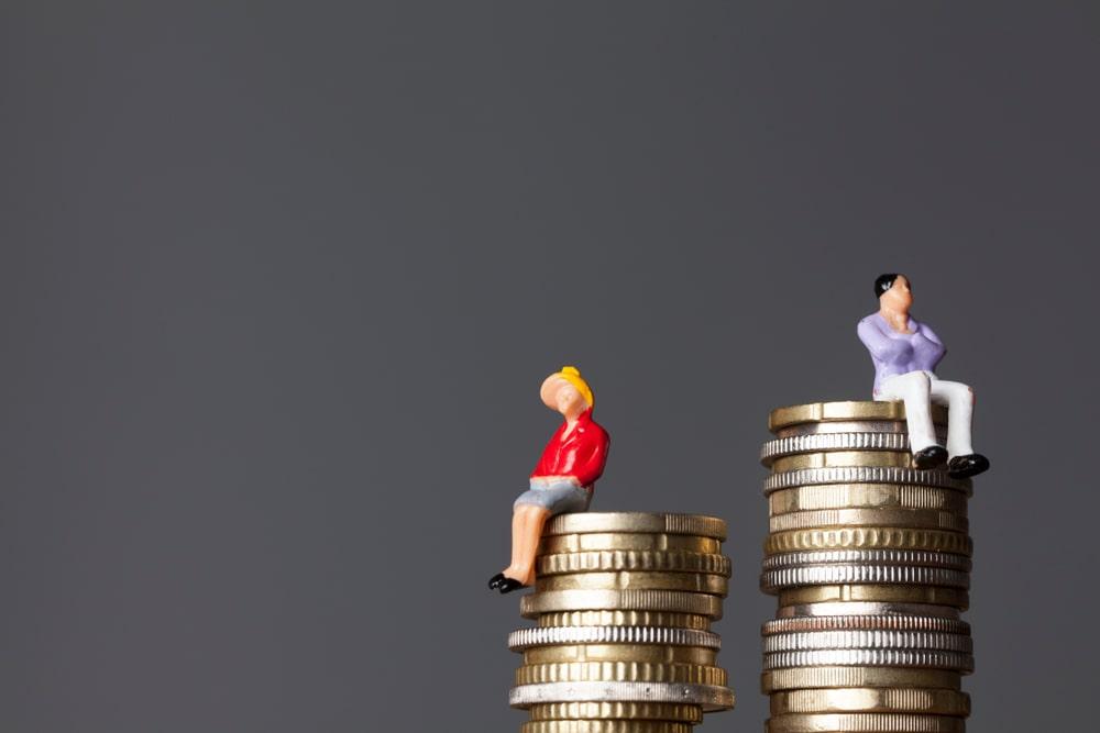 Donna e uomo seduti su pile di monete