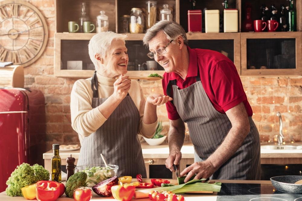 Senior che assaggiano dei cibi mentre cucinano