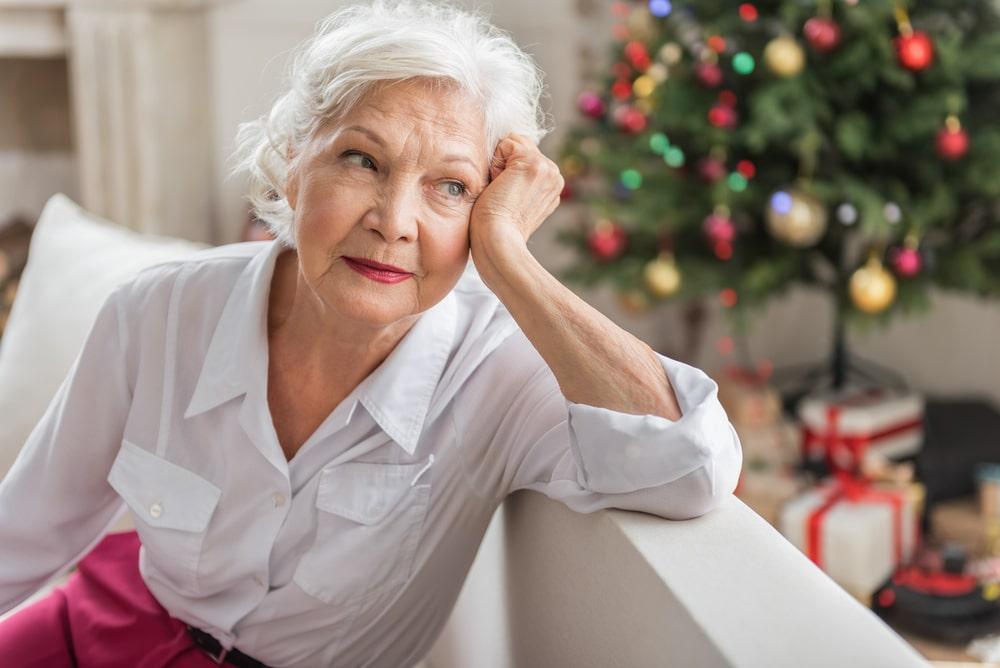 Donna senior pensierosa con sullo sfondo albero di Natale