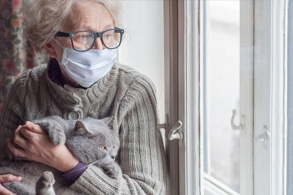 Donna anziana con gatto alla finestra