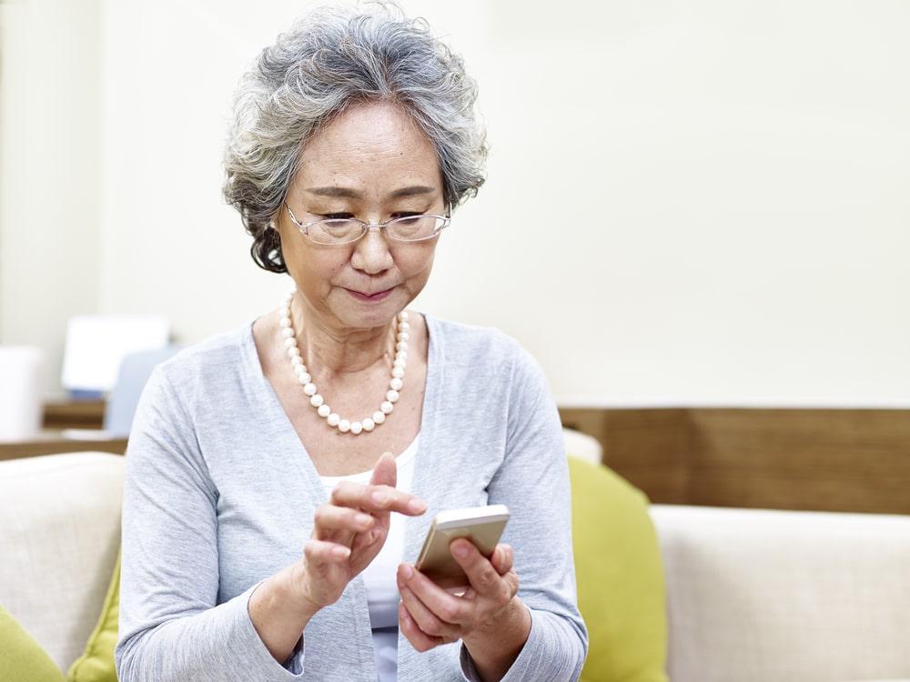 Senior cinese con smartphone
