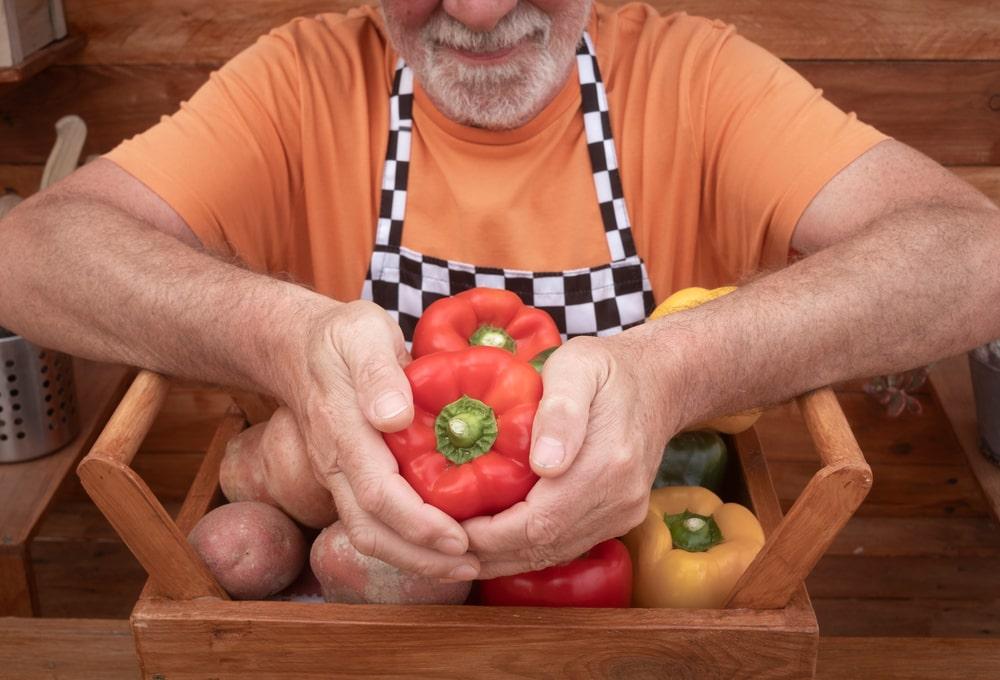 Agricoltore senior fa vedere i peperoni che ha coltivato