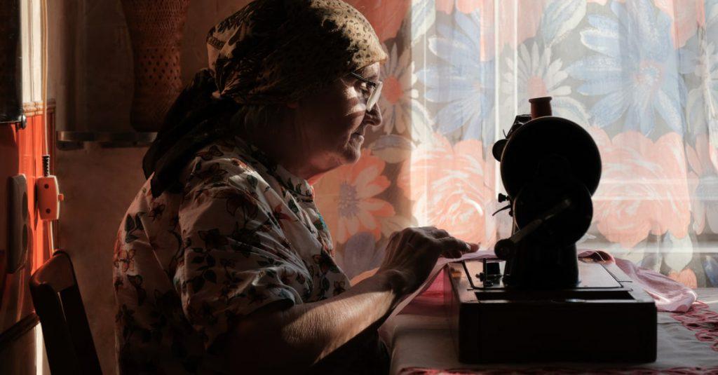 signora anziana con macchina da cucire