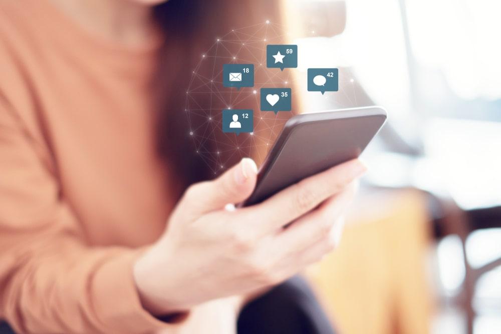 Simboli social che escono da uno smartphone