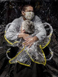 L'abbraccio tra un'infermiera e una donna anziana