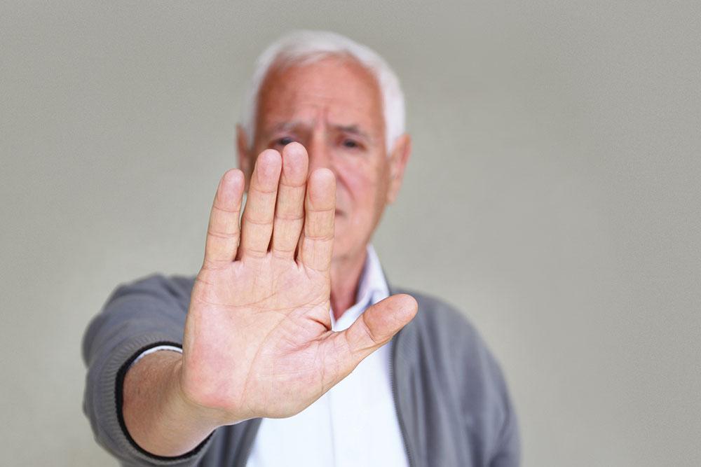 Un uomo alza una mano in segno di stop