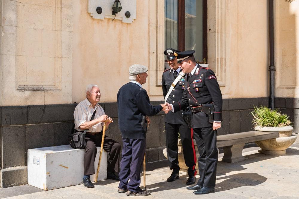 Carabinieri stringono la mano a un senior