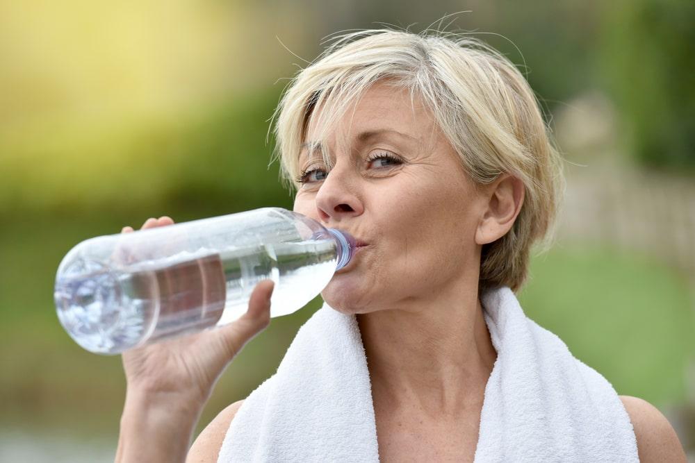 Una donna beve acqua dalla bottiglietta