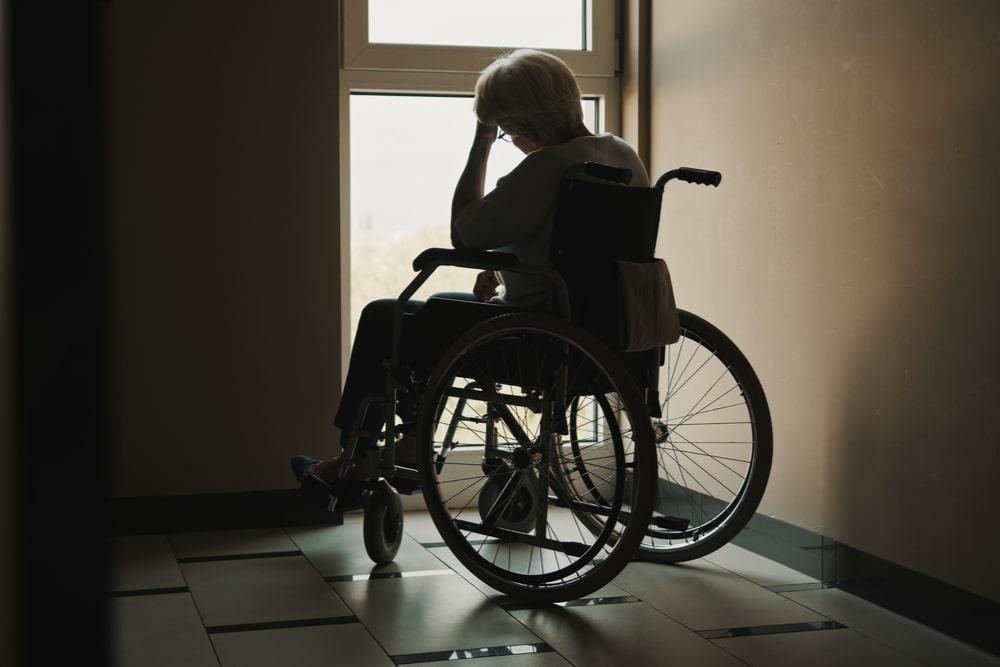 Una donna in sedia a rotelle guarda fuori dalla finestra