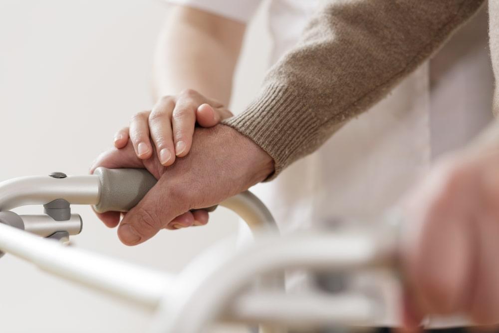 Le mani di un anziano e di un assistente