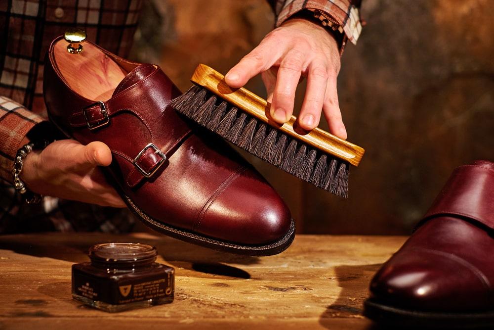 Un uomo lustra un paio di scarpe