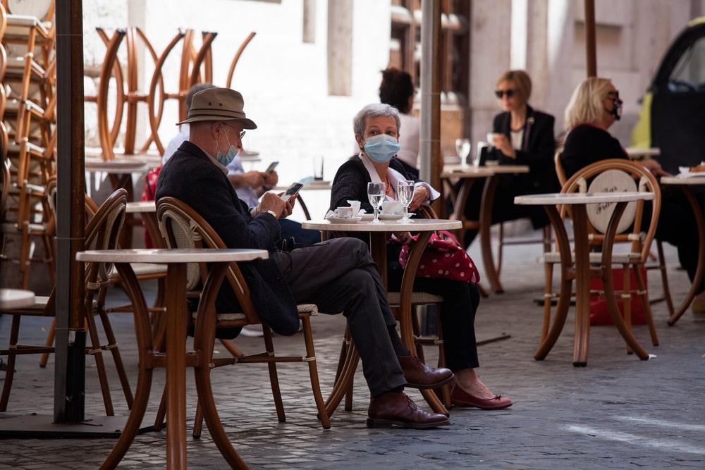Un uomo e una donna al bar con la mascherina