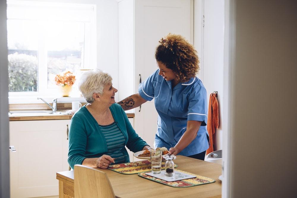 Una caregiver accudisce un'anziana