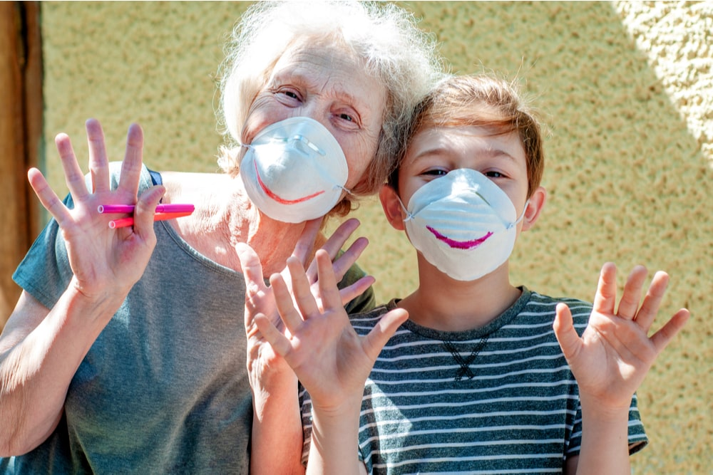 Una nonna e un nipote che indossano due mascherine con il disegno del sorriso